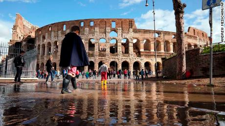 Children play on Tuesday in a puddle from the ancient Colosseum in Rome, one day after strong winds and rain struck the city.