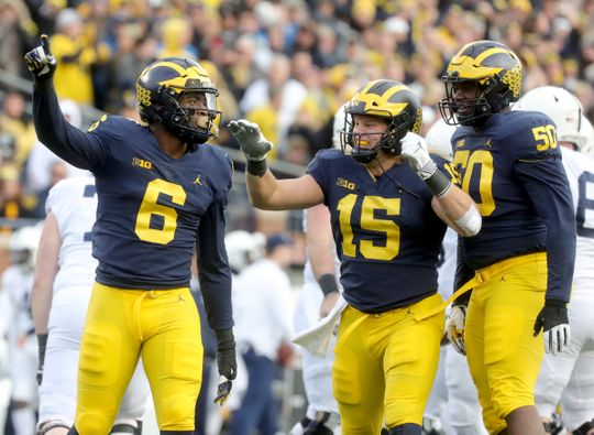 Chase Winovich, Michigan, center, celebrates his bag against Penn State with his teammates.