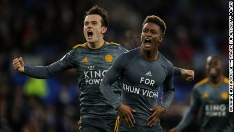 Demarai Gray is celebrating with his teammate Ben Chilwell, revealing a commemorative message for Vichai Srivaddhanaprabha during the Premier League match between Cardiff City and Leicester City.