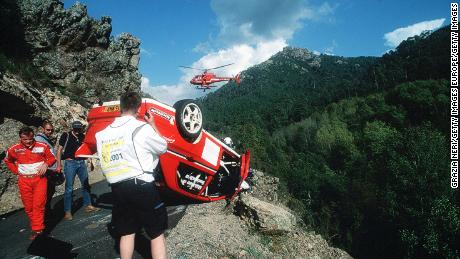 Mäkinen (left) inspected his car after a crash during the Corsica Rally in 2001.