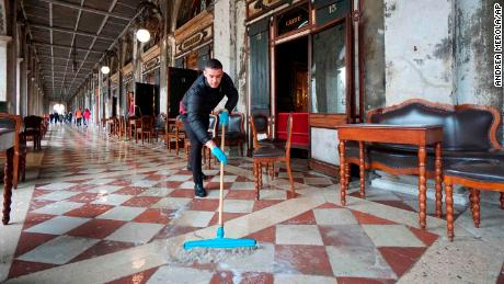 A man brushes the floodwater outside the historic Caffe Florian in St. Mark's Square on Tuesday.