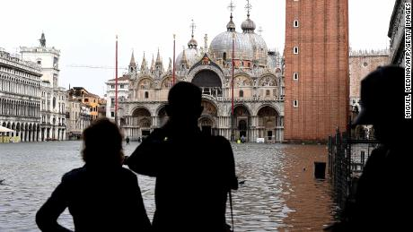 Tourists take pictures at the flooded St. Mark's Square during a high-level alert in Venice on October 29, 2018.