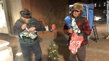 Two homeless people open gifts received by Rodney Smith Jr.