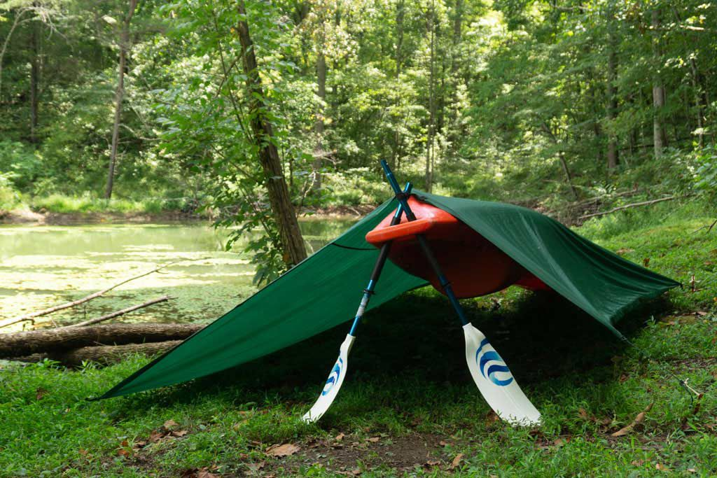 Using a kayak along with a broken paddle is another way to create a tarp easily and quickly.