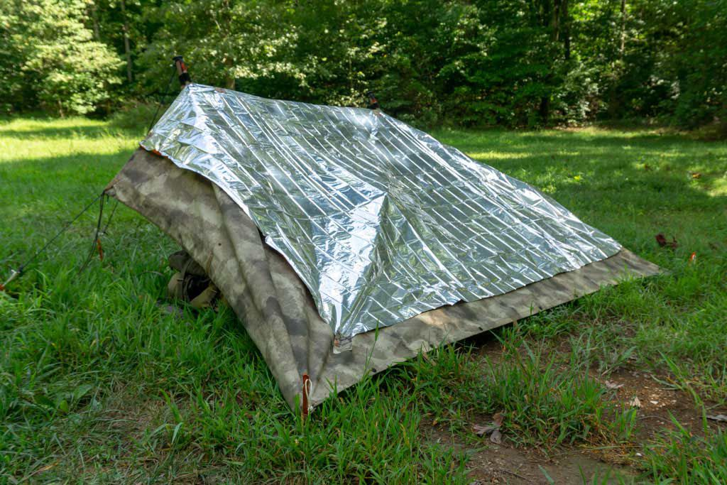 Using a thermal blanket on the back of a nice, thick tarp reflects the heat away from the shelter.